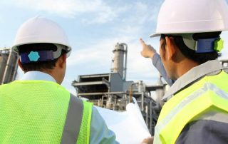Workers reading blue print at industrial complex