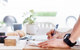 Image of person writing down their finances on paper